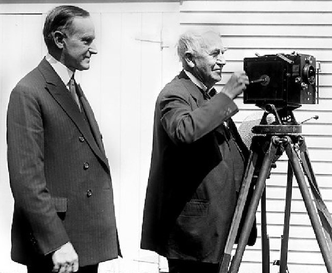 23-US President Calvin Coolidge looks on as Thomas Edison operates his first generation movie camera.jpg